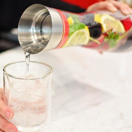 Grosche-rio-water-and-fruit-infuser-being-held-on-white-marble-counter-and-pouring-water-into-glass